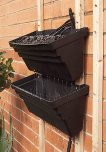 Water draining from one vertical gardening pot to another.